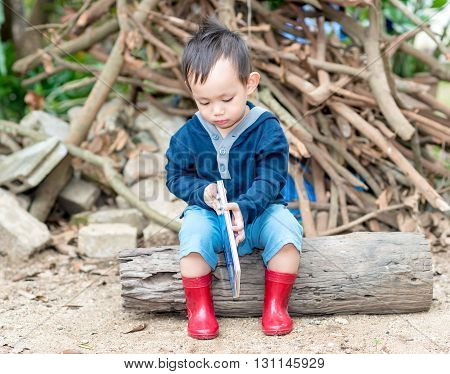 Asian Baby Boy  Reading Tale Book ,the  Boy Wear Red Boot Sitting On A Log .