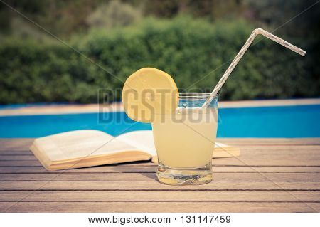 Glass of fresh lemonade and a book on the table at the poolside. Healthy lifestyle and summer vacation concept.