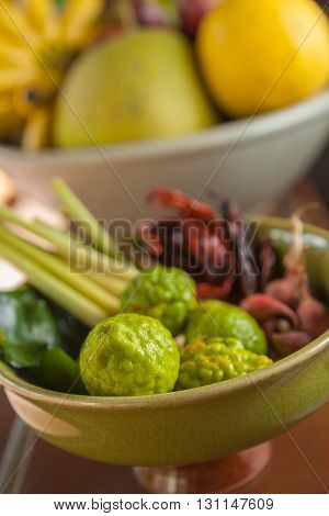 Thai and asian food ingredients in bowls bergamots dried chillis lemons limes lemongrass banana pomelo selective focus on the closest bergamot on the lower part of the frame leaving background blurred