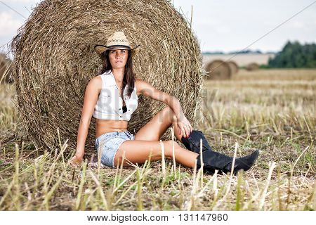 Woman in cowboy hat at a field.