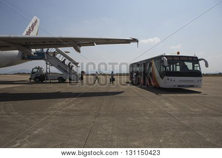 Binh Dinh, Vietnam - Apr 20, 2016: Passenger step out of an aircraft of VietJet Air carrier airline and catch a bus at Phu Cat airport. Vietjet Air is a low cost private airline carriers in Vietnam.