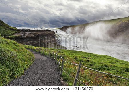 Fantastically spectacular cascading waterfall Gyullfoss. On the coastal slope paved walking trail