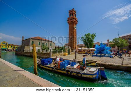 MURANO, ITALY - JUNE 16, 2015: Brick tower with the clock and glass sculpture on the side, fishingman using boat transportation near this on Murano.
