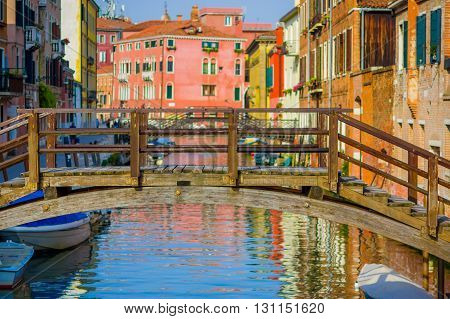 VENICE, ITALY - JUNE 18, 2015: Boats parking on the sides of water canal in Venice, colored buildings behind.