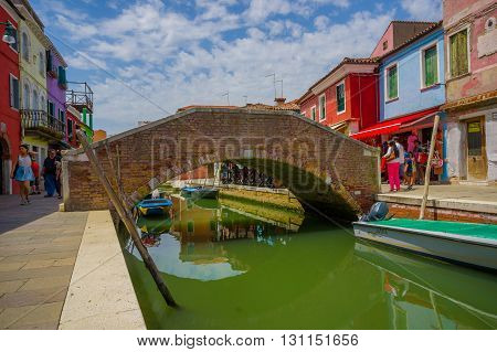 BURANO, ITALY - JUNE 14, 2015: Lovely nice bridge in the middle of water canals in Burano, color houses on the sides.