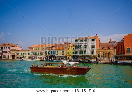 MURANO, ITALY - JUNE 16, 2015: Spectacular view of Murano city from the sea, traditional arquitecture with a boat sailing near the port.