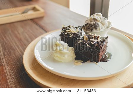 Chocolate brownies. Ice cream with brownies. Homemade brownies with vanilla ice cream and almonds sliced