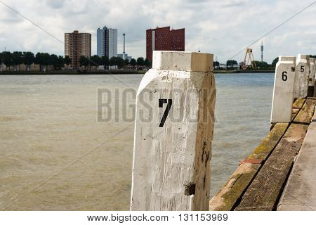 Numbered white painted bollards placed obliquely at a Rotterdam quayside. Many high offices and apartment buildings are newly constructed across the Nieuwe Maas.