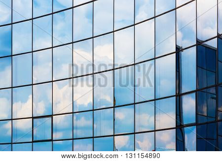 Facade of a modern office building. Modern industrial building with glass. Reflection of blue sky with clouds in the windows.