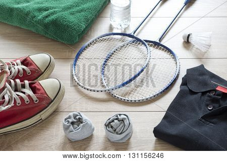 Rackets for badminton, shuttlecock, polo shirts, shoes, towel and water on a wooden floor.