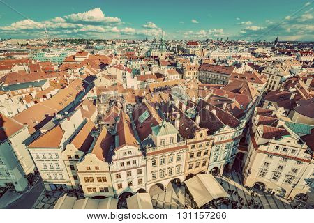 Cityscape of Prague, Czech Republic. View on traditional red roof tenement houses as seen from Old Town City Hall. Blue sunny sky, wide angle skyline. Vintage