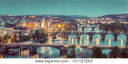 Prague, Czech Republic bridges panorama with historic Charles Bridge and Vltava river at night. Vintage