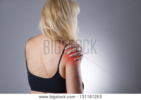 Woman with pain in shoulder. Pain in the human body on a gray background with red dot