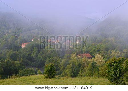 VETRINTSI VILLAGE, VELIKO TARNOVO PROVINCE, BULGARIA - MAY 8, 2016: Foggy morning in the mountain village in the Balkans