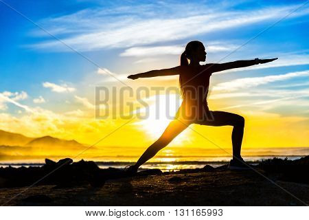 Silhouette of fitness athlete practicing warrior II yoga pose meditating at beach sunset. Woman stretching doing morning meditation against colorful sky background. Zen wellness and wellbeing concept.
