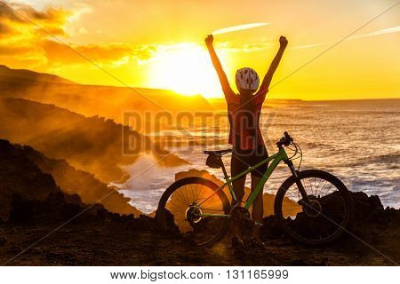 Success, achievement, accomplishment and winning concept with cyclist mountain biking. Winning happy MTB woman cycling reaching goal raising arms at sunset cheering and celebrating at summit top.