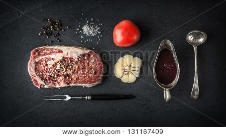 Piece of ribeye steak marble tomato and garlic on blue schist horizontal