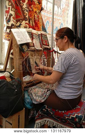 KUSADASI, TURKEY - JUNE 16, 2005: Unidentified Turkish woman weaves rugs as the souvenirs