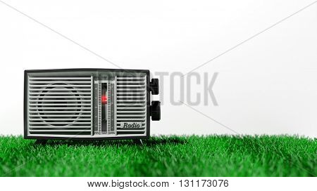 Antique radio transistor on grass, on white background with copy-space. 3D rendering