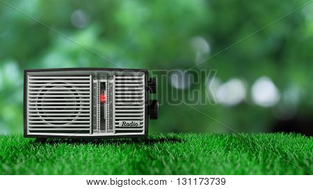 Antique radio transistor on green grass and green bokeh background. 3D rendering