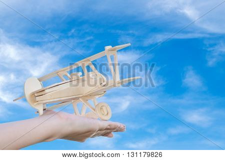 Closeup wooden plane in woman hand with blue sky background