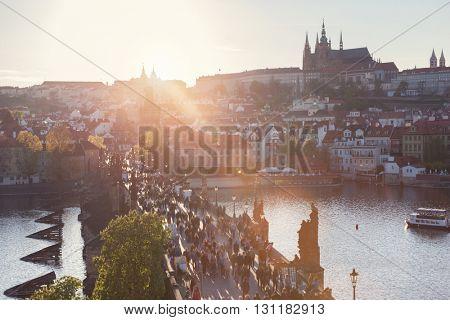 Charles Bridge on Vltava river in Prague, Czech Republic at sunset. View on Prague Castle, Hradcany. Sun flares.