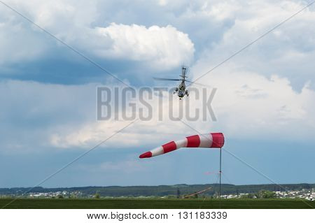 Green military helicopter flying near the ground roll forward from the weather vane