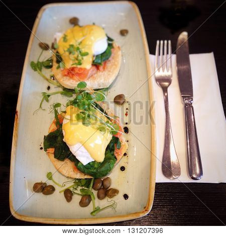 Eggs Benedict with salmon (also known as Eggs Atlantic, Eggs Hemingway, Eggs Copenhagen, Eggs Royale and Eggs Montreal) topped with microgreens, hollandaise sauce and capers.