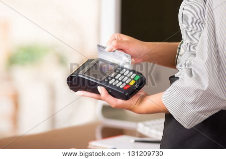 Close up of credit card machine, a woman hand swaping a gray card.