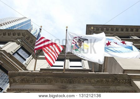 Flags of The United States, Illinois State and Chicago are seen hanging on John B Murphy Memorial building in Chicago. Designed in French Renaissance style, it hosts major events in the city.