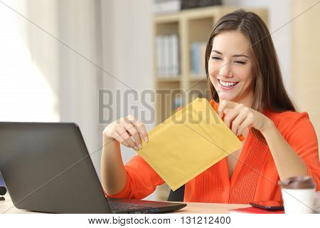 Freelancer opening a padded envelope in an office or home