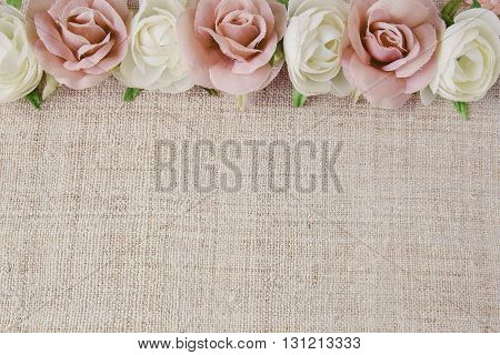 Artificial pink white rose flowers on linen copy space background selective focus vintage tone
