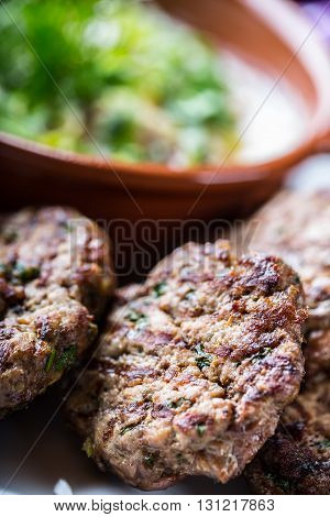 Burgers. Grill burgers. Minced burgers. Roasted burgers with grilled vegetable and herb decoration. Minced meat grilled in a hotel or restaurant.