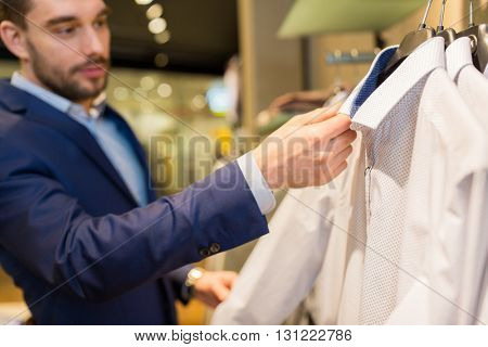 sale, shopping, fashion, style and people concept - close up of young man in suit choosing shirt in mall or clothing store