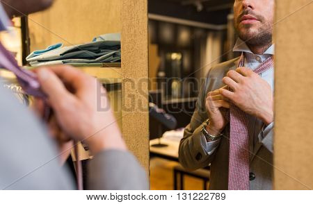 sale, shopping, fashion, style and people concept - close up of young man in suit choosing and tying tie and looking to mirror in mall or clothing store
