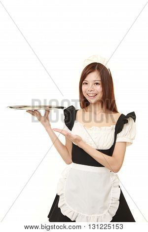 portrait of young Japanese woman wearing french maid costume presenting and showing something on white background