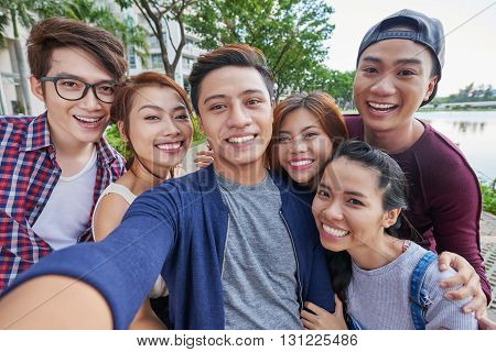 Vietnamese group of friends taking selfie together outdoors
