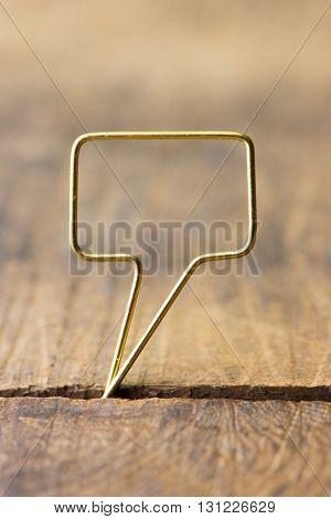 Blank golden speech bubble. Speech bubble made of gold wire on rustic grunge wood. Shallow depth of field.
