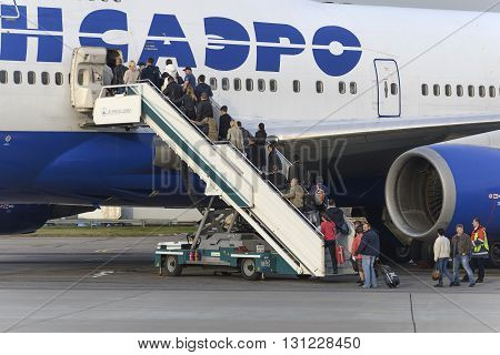 MOSCOW, RUSSIA - SEPTEMBER 26, 2014: Passengers climb the ladder into the plane Boeing 747 Transaero airlines. Transaero Airlines has ceased to exist in 2015.