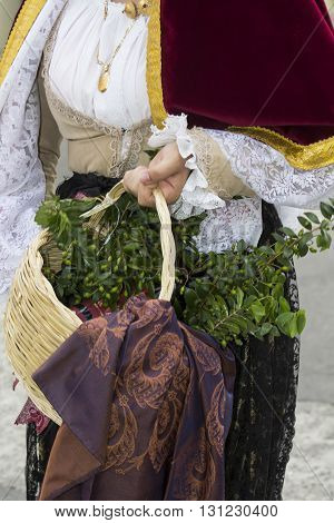 QUARTU S.E., ITALY - September 21, 2014: Parade of Sardinian costumes and floats for the grape festival in honor of the celebration of St. Helena. Wicker basket with Sardinian products handheld by a girl in Sardinian costumes