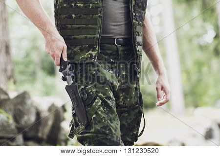 war, army, cold steel arms and people concept - close up of young soldier, ranger or hunter hands taking out knife in forest