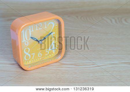 Orange alarm clock on wood background,Close up orange alarm clock