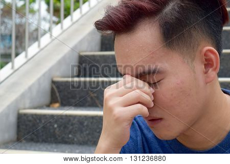 Young asian male with mild acne looking sad