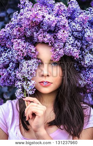 Portrait of a beautiful young girl in a wreath of lilac. Close-up.