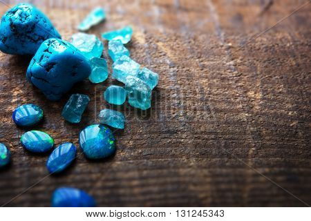 Treasure hunting. Mining for gems. Blue gems on rustic wooden table. Blue Turquoise, blue opals and apatite stones on a wooden table. Shallow depth of field.