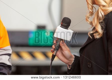 Press interview. Female reporter holding a microphone conducting an TV or radio interview.