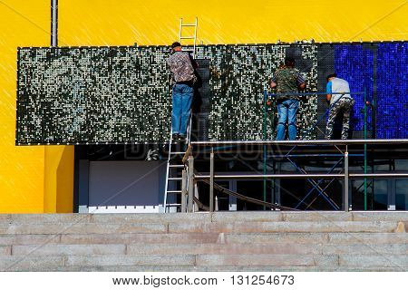A group of workers install an advertising billboard