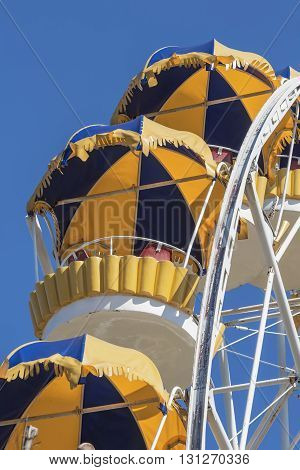Cabs Ferris wheel yellow-blue color on a background of blue sky