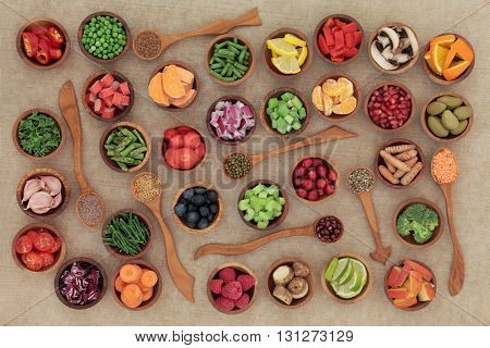 Healthy diet food selection in wooden bowls and spoons. High in antioxidants, vitamins, minerals and anthocyanins.