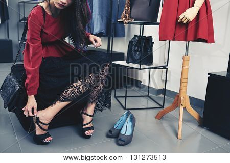 Cropped image of woman trying on heels in boutique poster